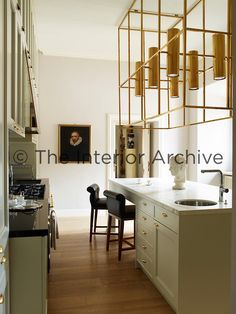 Simple Achille Salvagni designed the brass light fixture in this contemporary kitchen u