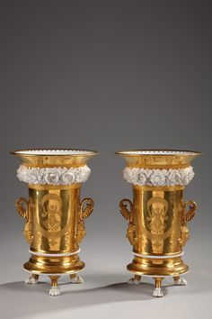 A pair of porcelain vases on paw feet provided with scrolled handles ending in stylized palmettes resting on masks. Gilded matting decoration, on one face winged putti holding draperies on..