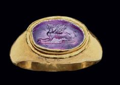 A ROMAN GOLD AND AMETHYST FINGER RING CIRCA 1ST CENTURY B.C. The hollow hoop rounded on the exterior, flat on the interior, with a flanged oval bezel set with a convex oval amethyst engraved with a female sphinx crouching to the left, on a ground line  | Christie's