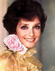 In March 1976, Audrey Hepburn Dotti, wearing a Valentino dress, poses for photographer Elisabetta Catalano at her Rome apartment. Audrey was wearing an evening gown by Valentino (strapless, of yellow chiffon with white polka dots, a rose of starched satin on the neck holding a long scarf in the same tissue of the gown and ornamented with small ruffles, a ribbon at the waist also in the same tissue, of his couture collection for the Autumn/Winter 1972/73).