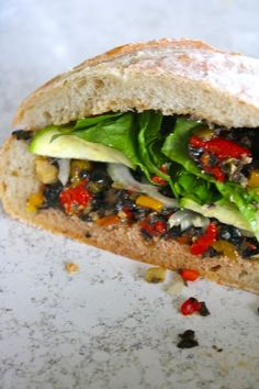 ITALIAN VEGGIE SANDWICH 2 small hearty Italian bread rounds or 1 regular-sized  4.25 ounce can chopped black olives  1/3 cup pimento stuffed green olives, chopped  1/2 cup bottled roasted red or yellow peppers, chopped  3 teaspoons red wine vinegar  1 large clove garlic, minced fine  Fresh onion slices  Fresh zucchini slices  Romaine lettuce