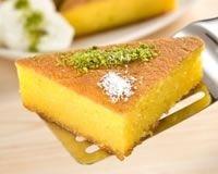 Gâteau de semoule au citron      6 oeufs      310 g de sucre en poudre      2 c. à café de zeste de citron finement râpé      80 ml de jus de citron      90 g de semoule      95 g de poudre d'amandes      2 c. à soupe de farine levante      125 ml d'eau