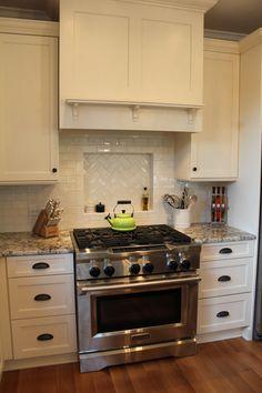 Granite color, stainless steel, white cabinetry, both subway tile and herringbone pattern for backsplash