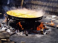 Giant paella cooking over wood fire