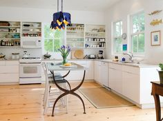 A pair of Petunia Pendants from Niermann Weeks' Amanda Nisbet Collection hang above the kitchen table in this Annapolis home. niermannweeks.com