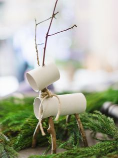 Add a playful touch to tabletop surfaces with reindeer made from recycled gift wrap tubes. To make, cut the tubes to size with a utility knife, allowing 4 inches of length for the body and 2 inches of length for the head. Next, cut twigs with floral shears, then add holes to the bottom of the 4-inch tube and along the top and the bottom of the 2-inch tube. Insert the twigs as legs, antlers and neck, then keep them firmly fastened with glue.