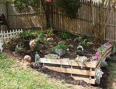great idea using pallets as a retaining wall flower bed. Line the inside with landscaping cloth, to keep the dirt where it belongs. you could also punch holes and plant on sides.