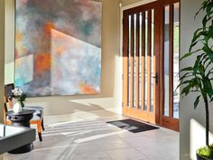 The bold artwork and interesting detailed door set the tone as you walk in this home's entryway.