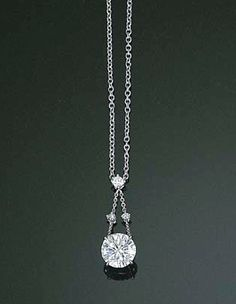 A DIAMOND PENDANT NECKLACE    The circular-cut diamond weighing 2.08 carats suspended from the diamond collet twin line surmount, to an oval-link neckchain, mounted in 18k white gold, 41.7 cm.