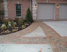 Creating designs with pavers makes this large driveway feel in scale with the home. Design by Rice's Nursery.