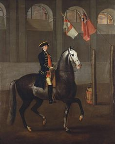 James Montagu(e) Morier; 1765 He was a Yeoman Rider to George III before joining the stable of the Prince of Wales in 1778. He is shown in the Riding House at Buckingham House, built for George III (1763-6) and now incorporated into the Royal Mews. It must date from the time of its completion (1765-6). Montague rides a grey horse, in profile to the right in a riding school, wearing a dark blue coat with gold trimming over a red waistcoat.