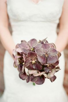 Finding winter wedding flowers can seem like a more difficult task, but fear not— we've put together 10 of our favorite bouquets, arrangements and boutonnieres that use their fair share of seasonal cold weather blooms. Pictured here: chocolate orchid wedding bouquet. Orchids bloom best in the cold months and make for a stunning bouquet. While the bright purple and pink varieties may seem a little too summery, these milk chocolate orchids are a luxe wintry option for your upscale bash.