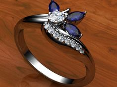 My personal favorite for a wedding ring! First glance literally took my breath away! Custom Diamond Engagement Ring with Marquise Sapphire Accents. $1,180.00, via Etsy.