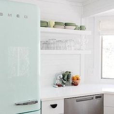 Pastel green Smeg Refrigerator in a charming cottage kitchen with tongue and groove walls and white floating shelves. Smeg Kitchen, Cottage Kitchen, Kitchen Decor, Green Kitchen, White Kitchen Tiles, White Floating Shelves, Kitchen, Tongue And Groove Walls, Smeg Refrigerator
