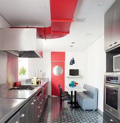 Com coifa aparente, acabamentos de aço inox e piso de ladrilho hidráulico, a cozinha é projeto da arquiteta Beatriz Fujinaka. Mesa comprida e banco estofado dão cara de lanchonete ao ambiente