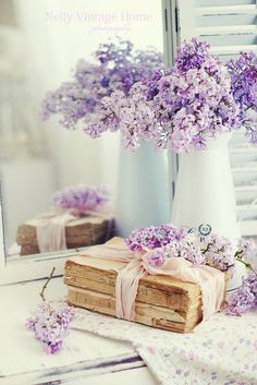Lilac bouquet in white pitcher, next to a bundle of vintage books...
