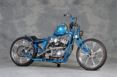 """Preggers - This eye catching machine has some original  rear suspension with a 45 degree upturn and then utilizing shocks mounted diagonally it almost approximates the lines of hard tail though it doesn""""t look like there is much wheel travel available.  The original Sportster frame loop is still intact up front of the seat post. The front suspension is fitted with a mountain bike shock absorber and a very unique structure as well. The Custom pregnant looking fuel tank is just short of round…"""