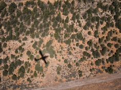 Shadow of an airplane over a remote and mountain area by Jean-Claude Manfredi for Stocksy United