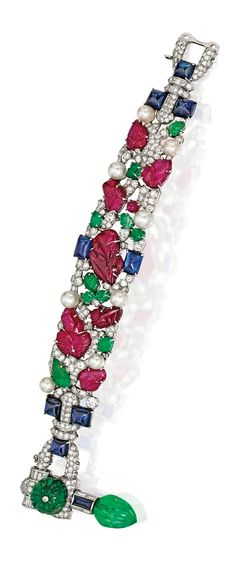 PLATINUM, CARVED COLORED STONE, DIAMOND & PEARL 'TUTTI FRUTTI' BRACELET, CARTIER.  The flexible openwork band set with carved rubies & emeralds, accented by cabochon rubies & sugarloaf cabochon sapphires, further set with diamonds, decorated with eight button-shaped pearls, the clasp completed by an articulated carved emerald drop, length 7 inches, signed Cartier, signature significantly rubbed; circa 1930.