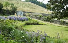 Modern Country Garden Design in Sussex with a posh shed and massed borders of grasses and perovskia to complement the rolling South Downs landscape by Sussex Garden Designers Acres Wild
