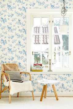 A whimsical wallpaper design featuring cute stylised birds and floral trails.