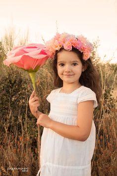 Niña con corona de flores de papel y rosa gigante