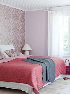 Sannan ja Timon makuuhuoneen seinä on tapetoitu Designers Guildin vaaleanpunaisella tapetilla ja ikkuna-seinä maalattu siihen sopivalla Tikkurilan maalisävyllä. Koristetyynyt ovat myös Designers Guildin mallistosta. Yöpöydän valaisimet on saatu lahjaksi perhetutulta. Kaksi-puolinen päiväpeitto on ostettu Moko Marketista ja viltti Stockmannilta.