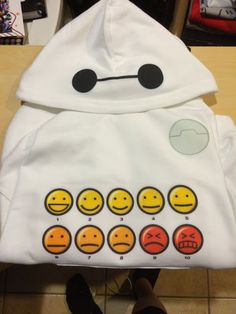 This Baymax-inspired hoodie features the healthcare robot's sweet face on the hood and his emoticon pain chart on the front. This chart just increases the Big Hero 6 hoodie huggable factorto level …