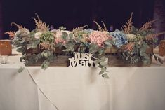 Top table flower arrangement. Hydrangeas and eucalyptus in a wooden crate - Image by Weddings Vintage - A Charlie Brear gown for a rustic wedding in Warwickshire at Shustoke Farm Barns. With hydrangea flowers and epic flower crown in pastel shades. With photography from Weddings Vintage.