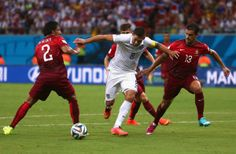 U.S. Stunned By Last-Minute Portugal Goal In World Cup Thriller - MANAUS, BRAZIL - JUNE 22: Clint Dempsey of the United States is challenged by Bruno Alves (L) and Ricardo Costa of Portugal during the 2014 FIFA World Cup Brazil Group G match between the United States and Portugal at Arena Amazonia on June 22, 2014 in Manaus, Brazil. (Photo by Warren Little/Getty Images)