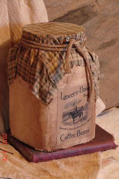Primitive Coffee Jar - Glass jar covered with tea stain material and aged label add green white checked material on top and tie w/ heavy string, add safety pin for a little bit of character