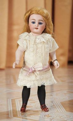 Large German All-Bisque Black-Stocking Doll, 886, by Simon and Halbig  painted thigh-high black stockings, brown two-strap shoes with sculpted bows, lace dress. Marks: 886 S 5 H (head) 5 (under arms). Comments: Simon and Halbig, circa 1890. Value Points: rare large size of the all-bisque doll, sought-after model, beautiful eyes.