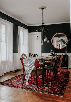Moody, eclectic dining room with black walls & mismatched wood chairs 🖤