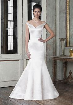 Sleek couture seamed fit and flare gown in silk cotton satin features a portrait neckline and chapel length train | Justin Alexander | https://www.theknot.com/fashion/9804-justin-alexander-signature-wedding-dress