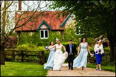 Laura, bridesmaids and parents on their way to the wedding ceremony at The Tithe Barn -
