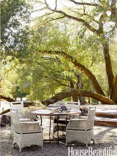 Oak trees shade a round table surrounded by wicker chairs — a favorite breakfast spot.