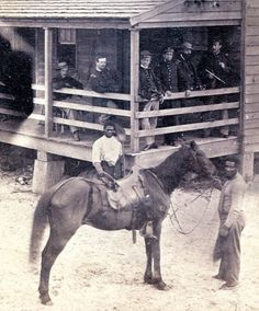 Free blacks in Union service. A pair of African American men—one holding a horse, the other a broom—pose in front of a group of Union soldiers. Free blacks served the Union forces in various capacities, from laborer to soldier.