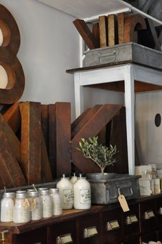 I am pretty sure I can recreate this look. Cardboard letters from craft store, some red/brown wood stain and maybe some silver oil paint. I'll have to give it a try.