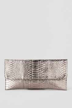 """We are wild about the Joella Metallic Snakeskin Clutch! Gold snakeskin embellishes this simple foldover clutch finished with a magnetic closure. This clutch goes perfect with a party dress & heels!<br />  <br />  - 12"""" width x 6"""" height<br />  - Imported"""