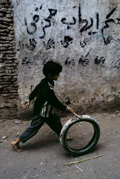 Steve McCurry: A young boy rolls an old tire down a street in Yemen. This simple game is played by children all over . In This World, We Are The World, People Around The World, Around The Worlds, Color Photography, Street Photography, Portrait Photography, Steve Mccurry Photos, Vivre A New York