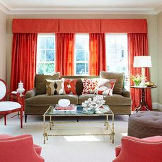 Soft neutral walls, a lush solid fabric on the sofa, and furniture with open legs and an airy design are key to keeping this living room's vibrant coral color scheme from overwhelming.