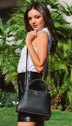 Miranda Kerr in a white top, black leather zip skirt and Louis Vuitton purse