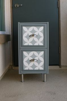 Soft grey and white paintwork with stylish graphic design on drawer front turns simple filing cabinet style unit into something rather special.