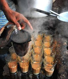 Hot tumblers of tea (called 'chai' in India) being served at a roadside tea stall in India.