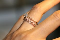 Rose gold diamond ring with multiple bands.