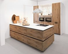 Warme houten keuken met wit blad. Mooie combinatie met witte vloer.