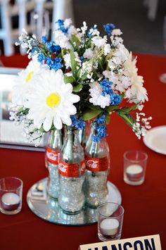 Classic Coke bottles are filled with white flowers and blue ribbons for Americana centerpieces - thereddirtbride.com - see more of this wedding here