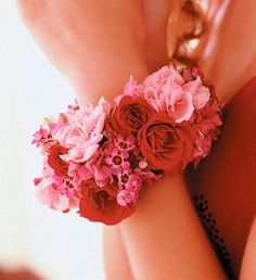 For Christina! (but in all white with silver accents to match her dress)  Set the trend with sizzling red spray roses and gentle pink flowers, wrapping her wrist like a glamorous bangle bracelet.