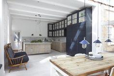 #reforma #cocina abierta en loft rehabilitado, isla y muebles bajos de madera natural, muebles altos con puertas de vidrio y armario color carbón, suelo de parqué.