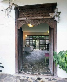 The sturdy double-door entrance is highlighted by a wooden fa�ade with a cherub hanging on a corner. The araal stone flooring begins from the outside and continues into the home.